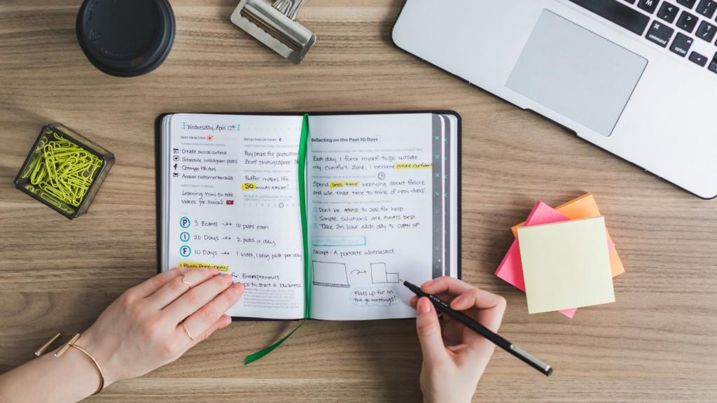 Pessoa fazendo anotações em uma agenda